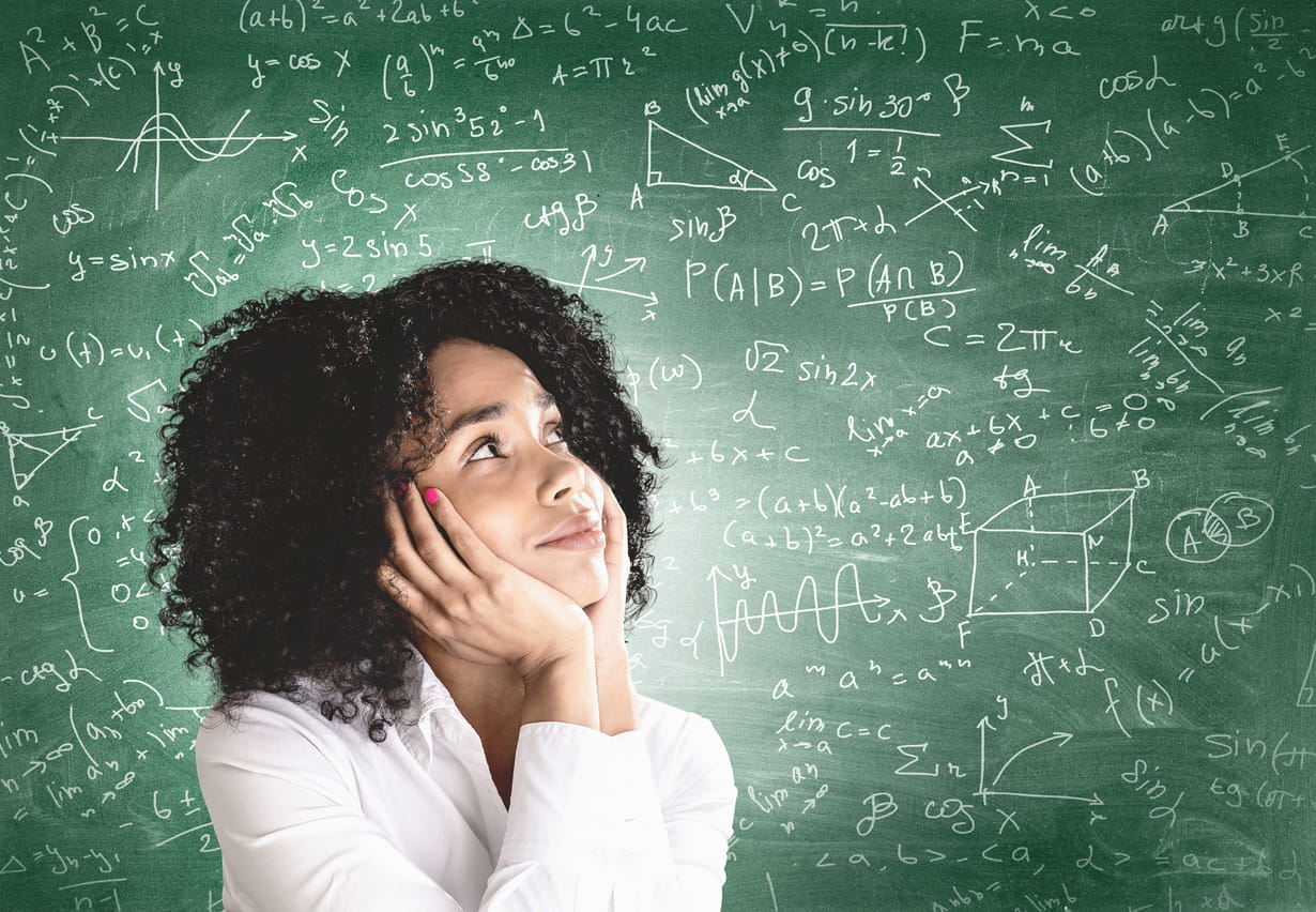Smiling young African American woman in white shirt looking at blackboard with formulas. Concept of education and science.